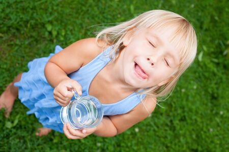 water garden: High angle view shot of blonde little girl wearing blue dress holding glass of water licking her lips with her eyes closed in a summer garden