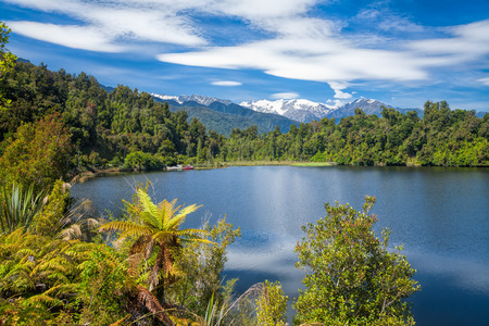 west coast: Sunny summer day on the Lake Mapourika on the West Coast of New Zealands South Island, a popular travel destination for fishing kayaking bird wathing and camping Stock Photo