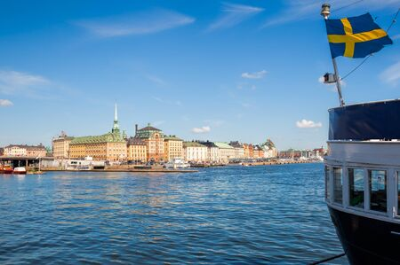 gamla stan: View of the harbour of Skeppsbron, the eastern waterfront of Gamla stan (the old town of Stockholm), with waving Swedish flag on moored ship in foreground