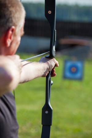 aiming: Man aiming bow at target outdoors