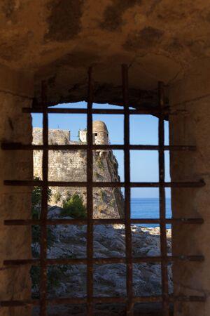 fortezza: Bastion of venetian citadel Fortezza in Rethymno, Crete, seen through grated window