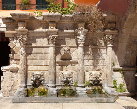 water town: Renaissance-style Venetian Rimondi Fountain springs drinking water through three lion heads in the centre of Rethymno old town, Crete Stock Photo