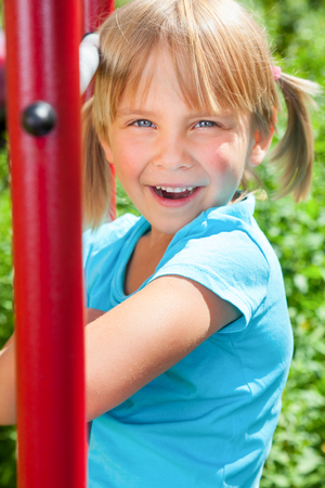 Portrait of cute blond girl with blue eyes wearing blue tshirt sitting on monkey bars on a summer day. Girl looking at camera smiling. The climbing frame is located in the courtyard of a house Stock Photo