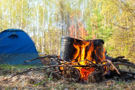 utensilios de cocina: Calderos sobre hoguera ardiente con la tienda de campaña en el fondo
