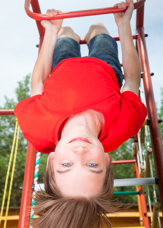 jungle gym: Low angle view of cute teen boy wearing red tshirt hanging upside down from a climbing frame in a playground looking at camera smiling