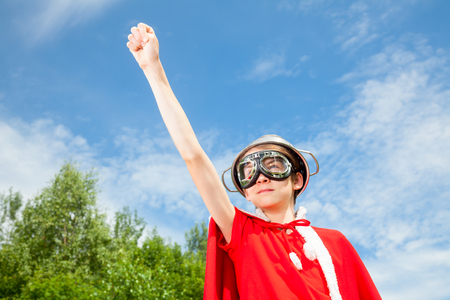 only one teenage boy: Low angle view of cute teen boy wearing metal colander as a helmet goggles and red costume - a funny power super hero child concept Stock Photo