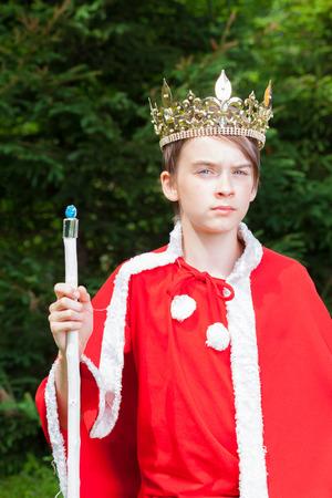 obey: muchacho adolescente linda con la corona y el traje rojo que sostiene un cetro que finge ser un rey Foto de archivo