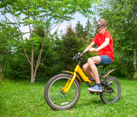 only one teenage boy: Cute teen boy wearing red tshirt and goggles riding a bicycle in a summer park looking at camera Stock Photo