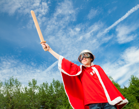only one teenage boy: Low angle view of cute teenage boy wearing metal colander as a helmet goggles and red costume holding wooden sword pretending to be a power super hero