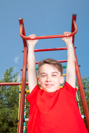 climbing frame: Low angle view of cute teen boy wearing red tshirt hanging  from a climbing frame in a playground looking at camera smiling