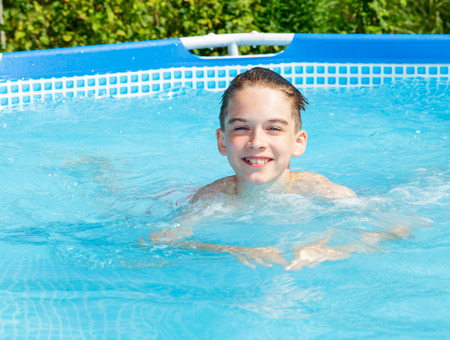 only one teenage boy: Cute teen boy enjoying summertime  swimming in a pool Stock Photo