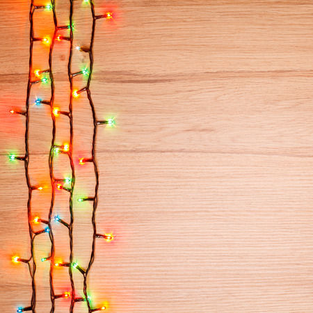 multicolored: Christmas lights of different colors on a wooden board
