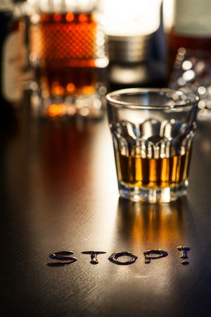 The word Stop on a bar with glass of alcohol in background Stock Photo