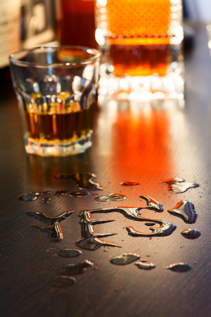 The word Yes written with spoiled whiskey on a bar counter Stock Photo