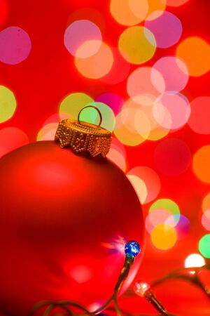 matted: Red christmas bauble with blurred lights in background