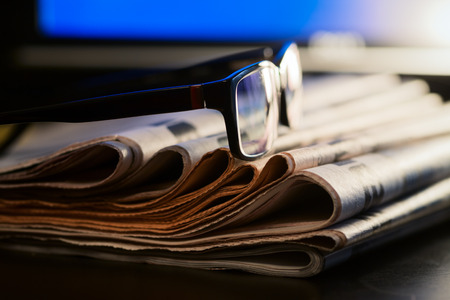 Glasses on stack of newspapers with blurred screen in background - News concept Stock Photo