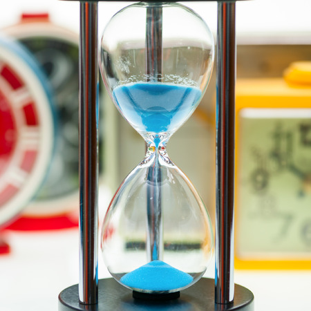 Hourglass with sand running through with blurred vintage mechanical alarm clocks in background
