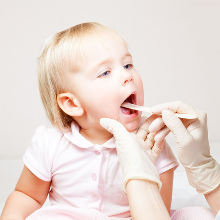 depressor: Pediatrician examines sitting child using wooden tongue depressor to check girls sore throat Stock Photo