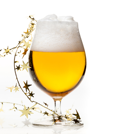 Full snifter glass of pale lager of beer with a large head of foam and golden christmas tinsel on white background Stock Photo