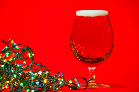 Full snifter glass of lager of beer with christmas lights on red background