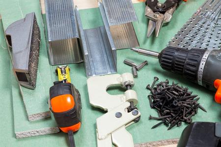 crimper: Plasterboard tools set with metal studs, screws, tape measure, screwgun and punch lock crimper Stock Photo