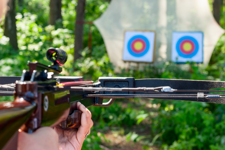 arbalest: Woman aiming crossbow at target outdoor Stock Photo