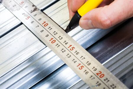 Person marking a  measurement on a metal stud with marker pen while constructing plasterboard frame