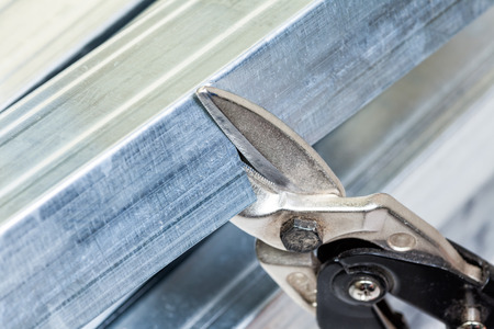 Person cuts a metal stud with snip cutter while constructing plasterboard frame Stock Photo