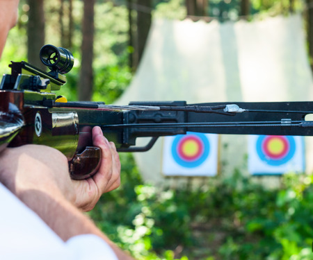 arbalest: Man aiming crossbow at target outdoor Stock Photo