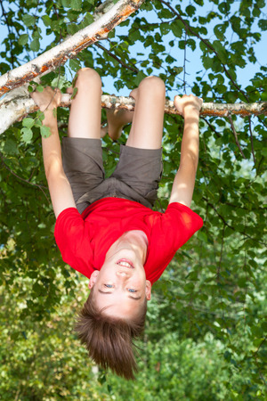Low angle view of happy teenager boy wearing red t-shirt hanging upside down from a birch tree looking at camera smiling enjoying summertime Stock Photo