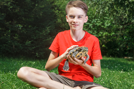 Cute teenager boy wearing red t-shirt sitting on a lawn in a summer garden holding turtle looking at camera smiling Stock Photo