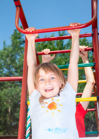 climbing frame: Low angle view of happy girl wearing hanging from a climbing frame in a playground looking at camera smiling enjoying summertime