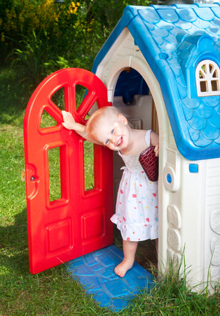 Little baby girl wearing white dress looking out from plastic play house doorway in a summer playground Stock Photo