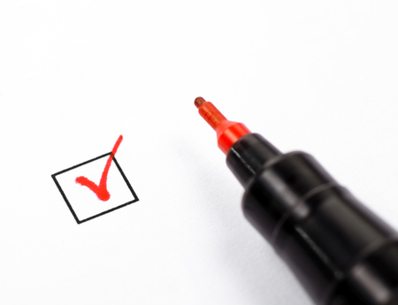 Close-up shot of filled check box and red marker Stock Photo