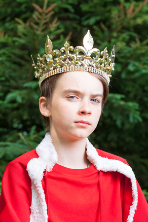 Portrait of teenager boy wearing crown and red cape pretending to be a king