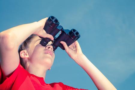birdwatcher: Low angle view of birdwatcher teen boy wearing red tshirt looking through binoculars at birds against blue summer sky