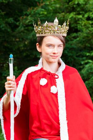 Roztomilý chlapec s teenagery na sobě korunu a červený kostým drží žezlo předstíral, že je král