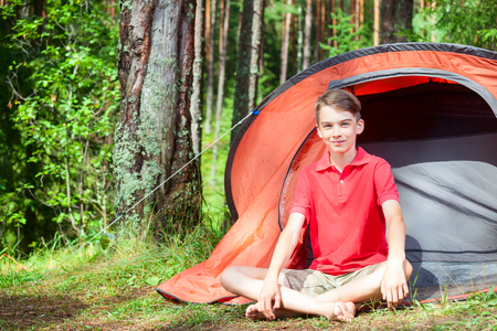 Happy teen boy sitting barefoot by a camping tent in a summer forest looking at camera smiling