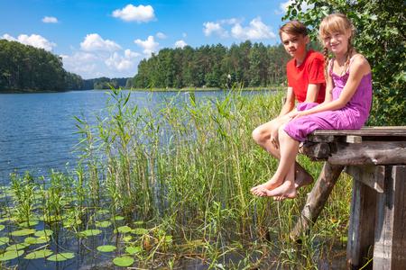 Teenager-Jungen und Mädchen im Grundschulalter auf einem Holzsteg von einem Wald-See sitzen Sommertag im Freien genießen Standard-Bild - 72142632