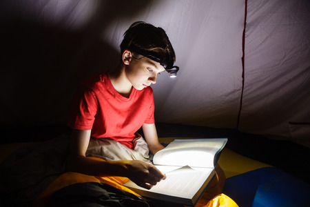 concentration camp: Teen boy sitting in a camping tent wrapped in a sleeping bag reading a book with flashlight on at night
