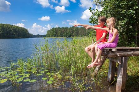 birdwatcher: Birdwatchers boy and girl sitting on a wooden pier by a summer lake observing birds Stock Photo