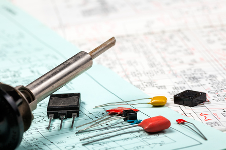 Soldering iron with electronic components on  electric schemes