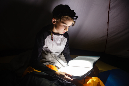 Teen boy sitting in a camping tent wrapped in a sleeping bag reading a book with flashlight on at night