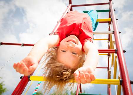 Low angle view of happy girl hanging from a climbing frame in a playground looking at camera smiling enjoying summertime