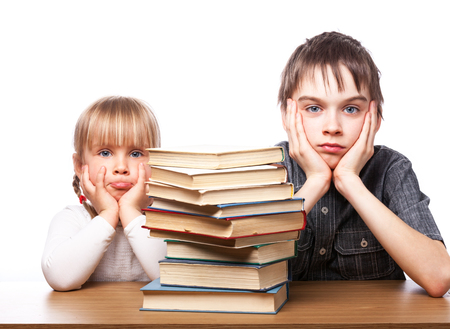 Portrait of frustrated boy and girl sitting at a desk with pile of books holding heads having learnind problems photo