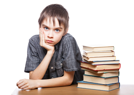 Portrait of frustrated schoolboy sitting at a desk with pile of books holding his head having learnind problems photo