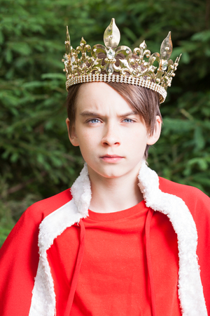 Portrait of teenager boy wearing crown and red cape pretending to be a king photo