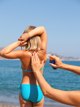 suncare: Mother spraying sunblock on her  daughters back before sunbathing on a beach