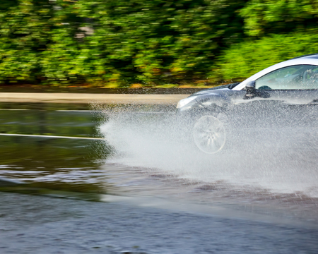 hydroplaning: Car moving through a puddle on a flooded street with the risk of aquaplaning