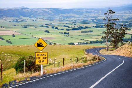 Curvy road with Steep Hill Descent warning road sign in New Zealand Reklamní fotografie